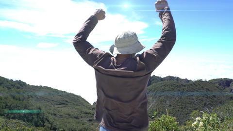 Man Reaching The Top of mountains. Raise up hands. Achievement concept, euphoria Live Action
