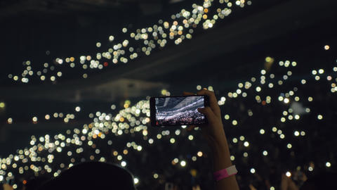 Audience with lights in concert hall and woman taking mobile video Live Action