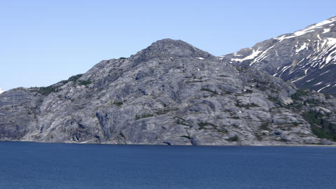 Traveling time-lapse of a rocky outcropping alongside the water in Glacier Bay,  Footage