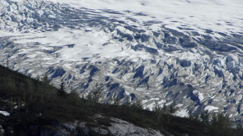 Traveling view of the side of a glacier and the side of a snow covered mountain  Footage