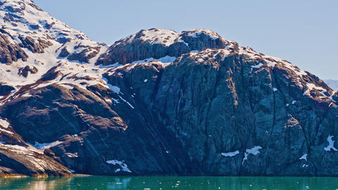 View from the side of a traveling cruise ship of snow covered rocky mountains al Footage
