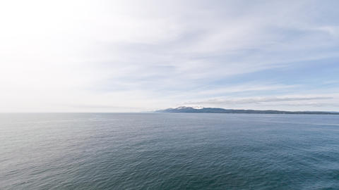 Time lapse of the ocean cloud formations with mountain ridge in the background,  Footage