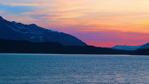 Traveling time-lapse of a sunset behind mountains and water near Haines, Alaska Footage