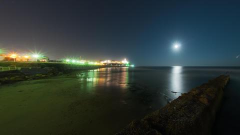 Beach footage of moon setting into the ocean near an Israeli city Footage