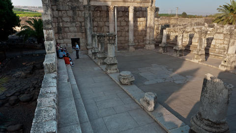 Time lapse of tour groups sitting and moving around synagogue ruins Footage