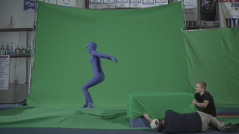 Performer in blue body suit does a backflip onto green block Footage