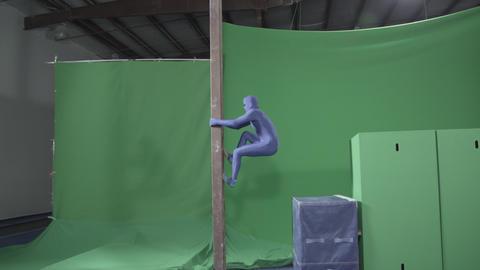 Slow motion green screen shot of a man pretending to be a ninja climbing a pole Footage