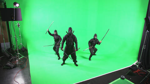 Static shot of three people dressed as ninjas posing in front of the camera Footage