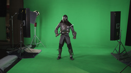 Front shot of man standing in armor holding sword, shot in slow motion against a Footage