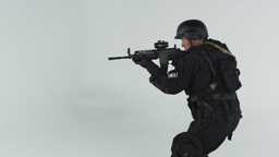 Shot of swat entering at right pointing an assault rifle. Shot in slow motion ag Footage