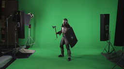 Front shot of model in armor holding an ax and shield. Shot in slow motion again Footage