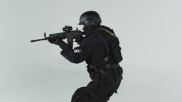Shot of swat entering right pointing an assault rifle. Shot in slow motion again Footage