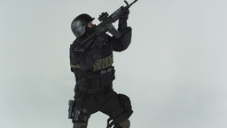 Shot of swat entering at the left with an assault rifle. Shot in slow motion aga Footage