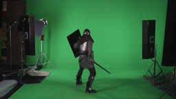 Back shot of man in armor holding sword and shield. shot in slow motion against  Footage