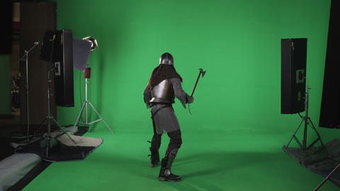 Back shot of man in chain mail holding an ax in hand. shot in slow motion agains Footage