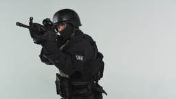 Shot of swat soldier with an assault rifle at ready. Shot in slow motion against Footage