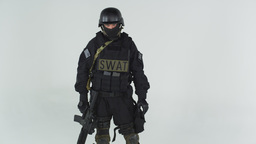 Head to knee shot of swat soldier holding rifle. Shot in slow motion against gre Footage