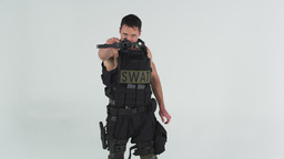 Shot of soldier pointing rifle with one hand at camera. Shot in slow motion agai Footage