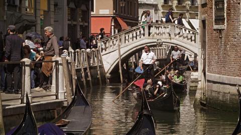 VENICE, ITALY - May 2: Gondolier steer's gondola under a bridge on May 2, 2012 i Footage
