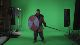 Shot of man standing dressed in armor, with helmet, sword and shield. Shot again Footage