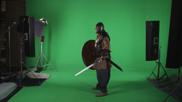 Side shot of man dressed in armor, with helmet, sword and shield. Shot against g Footage