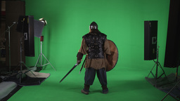 Back shot of man dressed in armor, with helmet, sword and shield. Shot against g Footage