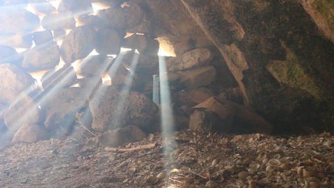 sun's rays pierce in the gaps between the stones in cave Footage