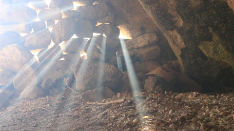 sun's rays pierce in the gaps between the stones in cave, Live Action