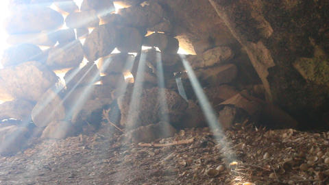 sun's rays pierce in the gaps between the stones in cave Stock Video Footage