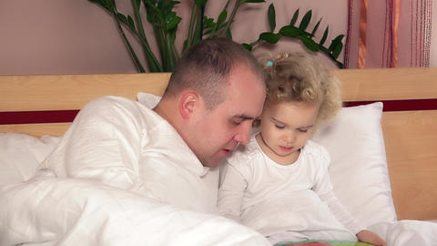 Happy family dad man and daughter girl reading tales from book GIF