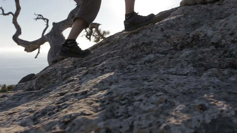 Dynamic following close-up shot of a man climbing a mountain. Detail of Footage