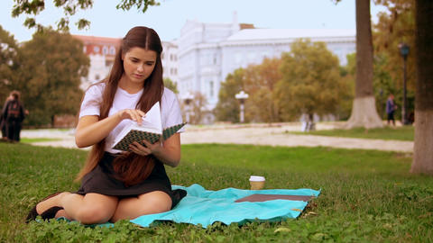 brunette girl reads book in park GIF