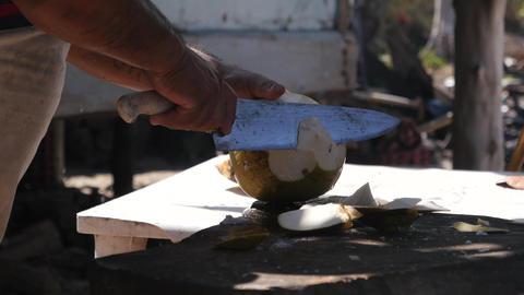 Man chopping a fresh coconut in Mexico GIF