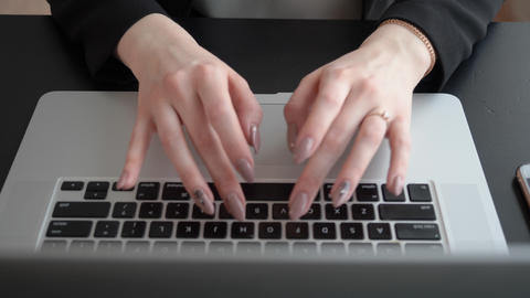 Female hands typing on notebook keyboard while work in modern business office Live Action