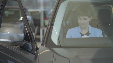 Young pretty woman in formal wear blue suit wear seat belt sitting inside car in Live Action