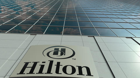 Signage board with Hilton Hotels Resorts logo. Modern office building facade Footage