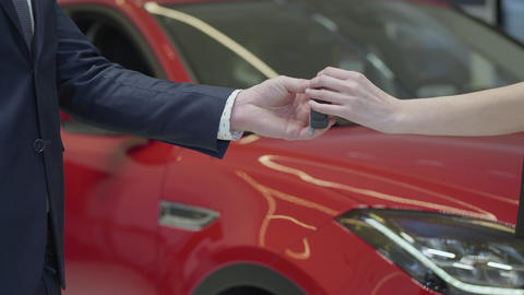 Unrecognized salesman gives a car keys to unrecognized businesswoman and shake Live Action