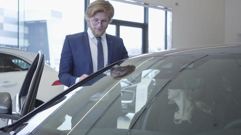 Handsome young car salesman discussing new automobile model in motor show. Car Live Action