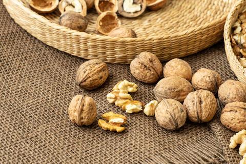 Walnuts on rustic natural burlap, Walnut kernels in wicker basket, Walnut background Photo