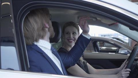 Happy successful couple sitting in passenger compartment of the new vehicle Footage