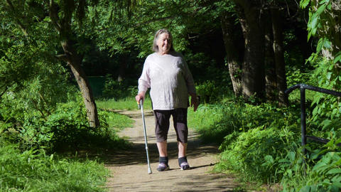 friendly, grandmother walk with cane on road. old person leaning on a walking Archivo