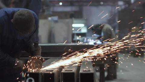 A man cuts metal with a circular saw, welding works are carried out in the Footage