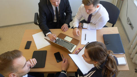 Business team working together and looking notebook at table in office Live Action