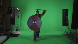 Shot of man dressed in armor, hitting his large round shield with sword. Shot ag Footage