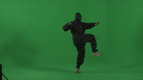Ninja dressed in black does barefooted round house kicks Footage