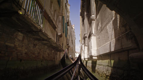 A gondola glides through a canal behind another gondola Footage