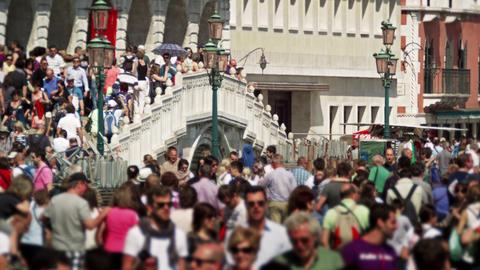 Slow motion shot of crowds walking across pedestrian bridge Footage