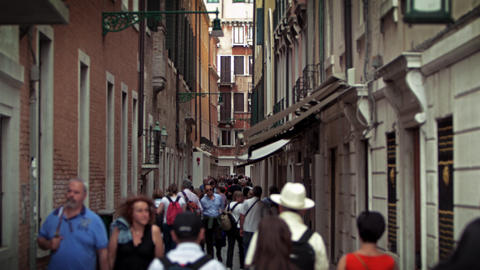 Slow motion shot of people moving down narrow street Footage