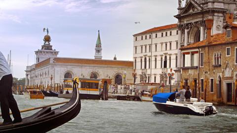Gondolier steers a gondola near Santa Maria della Salute Footage