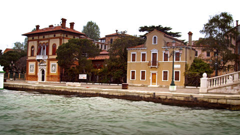 Tracking shot of bridge, boat, and buildings along a canal in Venice Footage